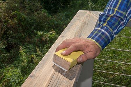Die Oberfläche eines Geländers wird geglättet