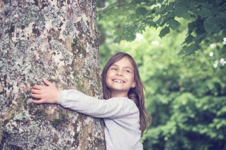 Kleines Mädchen umarmt einen Baum