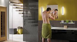 Mann vor Badezimmerspiegel mit Spiegelleuchte