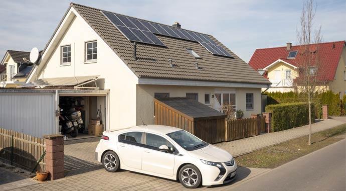E-Auto parkt vor Haus mit Photovoltaik-Anlage