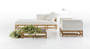 """Sofa und Sessel aus der Reihe """"easy pieces"""" präsentieren sich in hellem Mischgewebe, gerahmt von einem Gestell in Nussbaum."""
