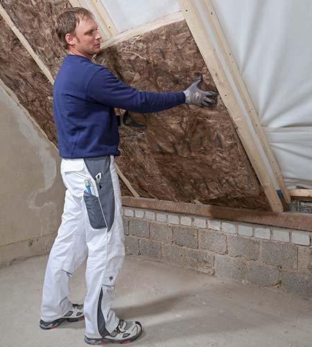 Handwerker verlegt die Zwischensparrendämmung Knauf Insulation aus Glaswolle