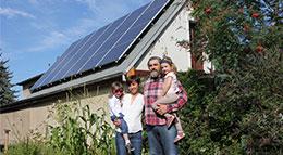 Familie vor ihrer Photovoltaik-Anlage