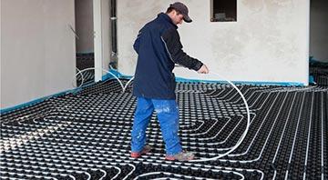 Handwerker der die Heizungsrohre einer Fußbodenheizung verlegt