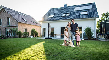 Baufamilie vor ihrem neuen Eigenheim