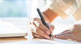 Frau beim Unterzeichnen eines Bauvertrags