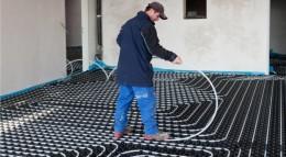 Die Heizungsrohre der Fußbodenheizung werden in Noppenplatten verlegt.