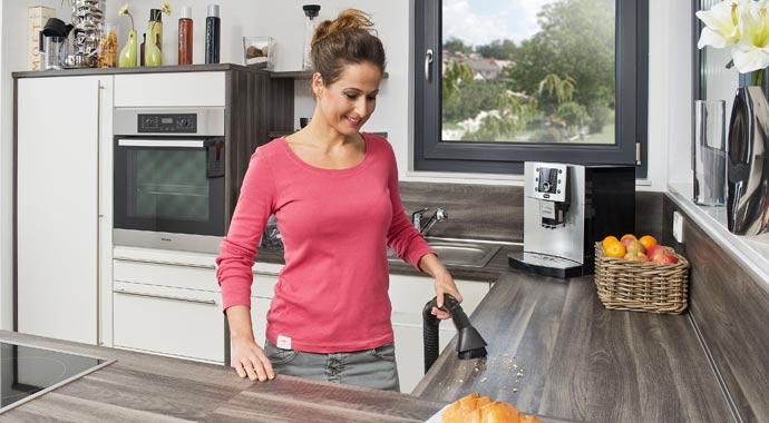Frau mit Zentralsauganlage in Küche