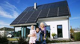 Familie vor ihrem Haus mit Photovoltaikanlage
