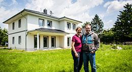 Zufriedene Bauherren vor ihrem neu errichteten Eigenheim